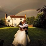 Bride and Groom kiss under a rainbow at wedding venue essex