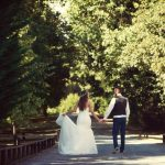 Couple walking down tree covered path at wedding venue essex