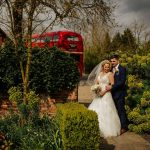 Couple standing on path by wall and red bus at wedding venue essex
