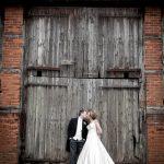 bride and groom kiss infront of barn door