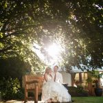 Bride and Groom sat on bench with sun shining between leaves