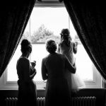 Bride, Bridesmaid and Child looking out of a window at wedding venue essex